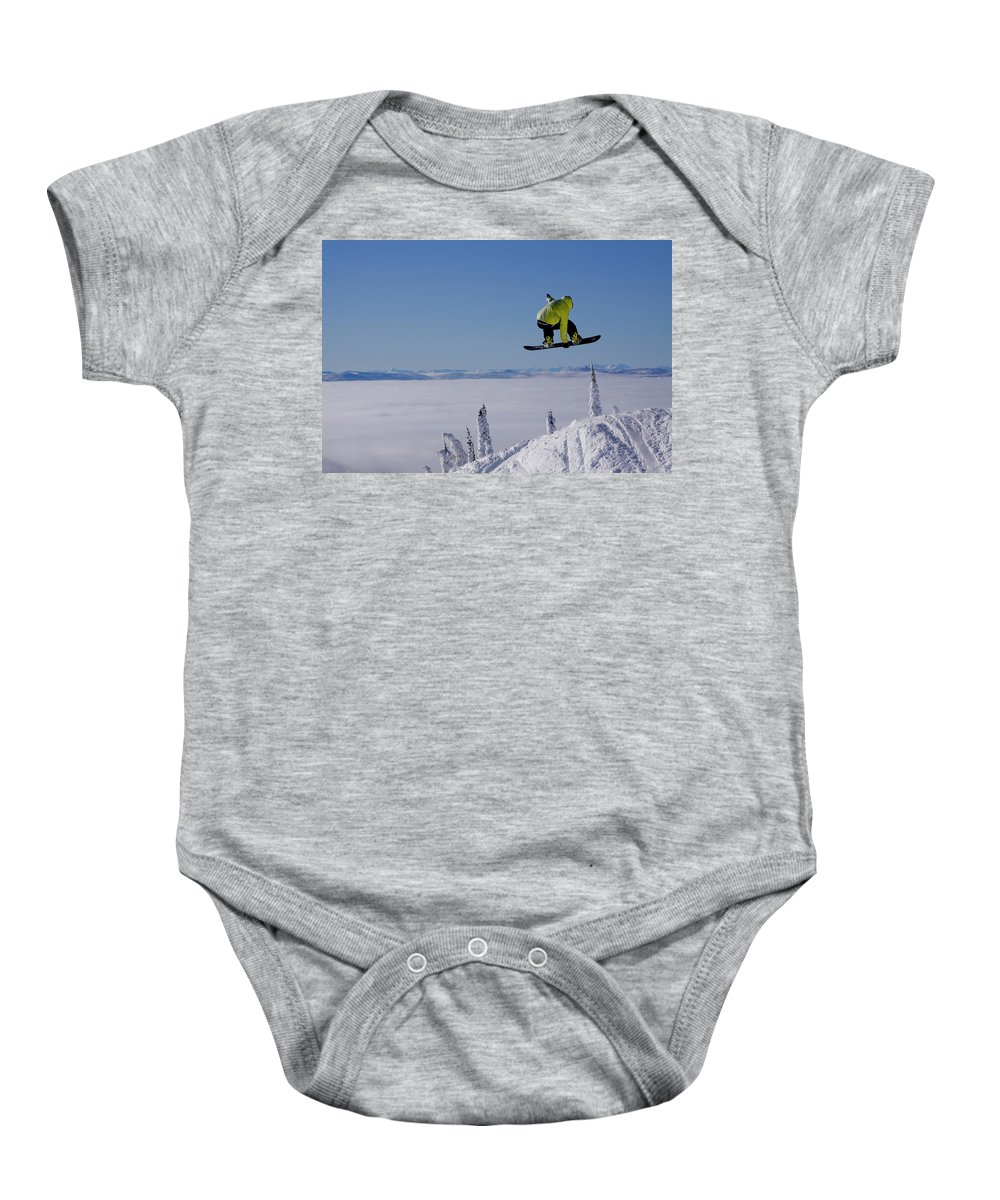 Adventure Baby Onesie featuring the photograph A Snowboarder Catches Air Off A Jump by Noah Couser