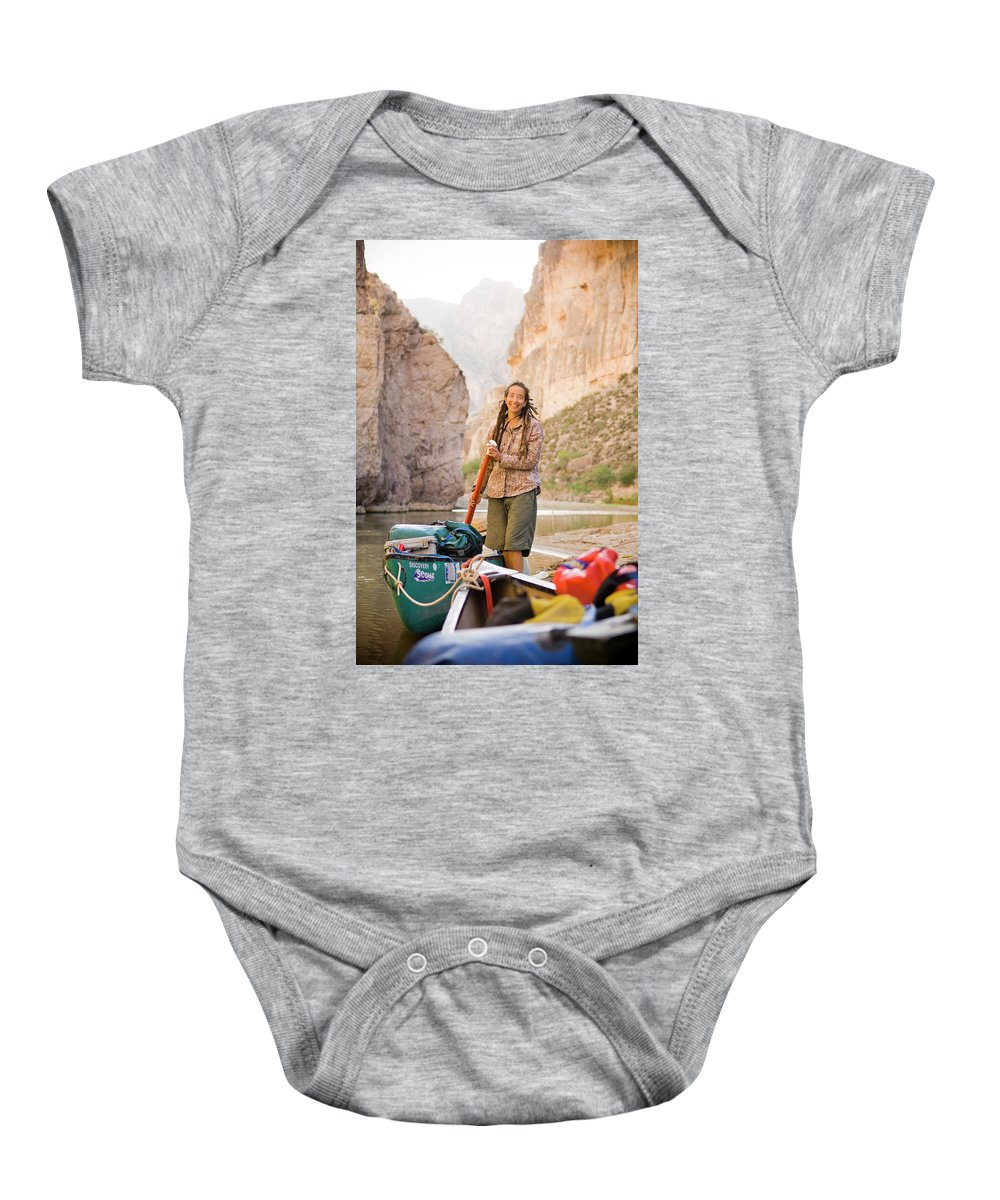 Adventure Baby Onesie featuring the photograph A Woman Unloads Gear From Her Canoe by David Nevala