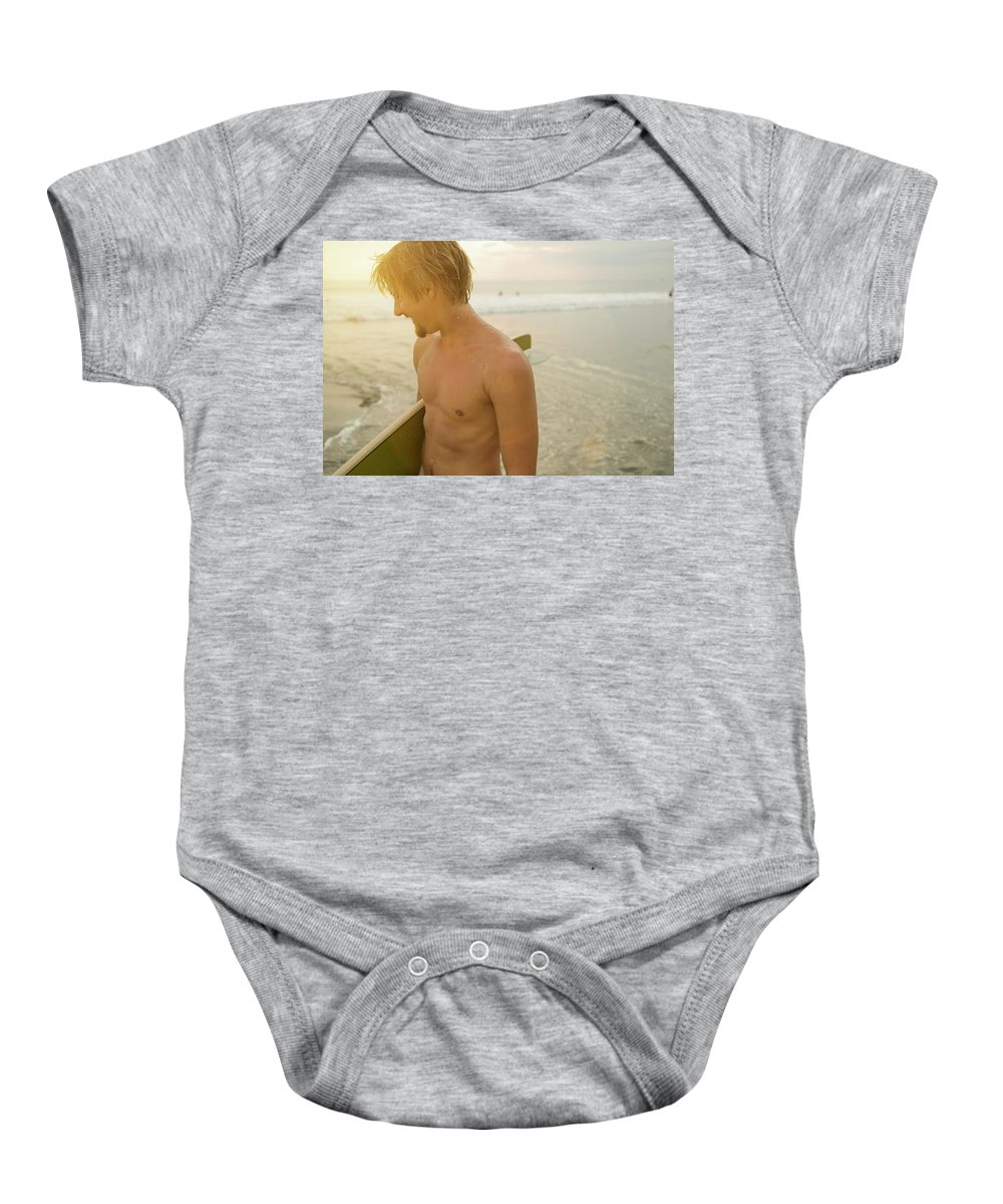 20s Baby Onesie featuring the photograph A Young Man Holds A Surfboard by Lacey Ann Johnson