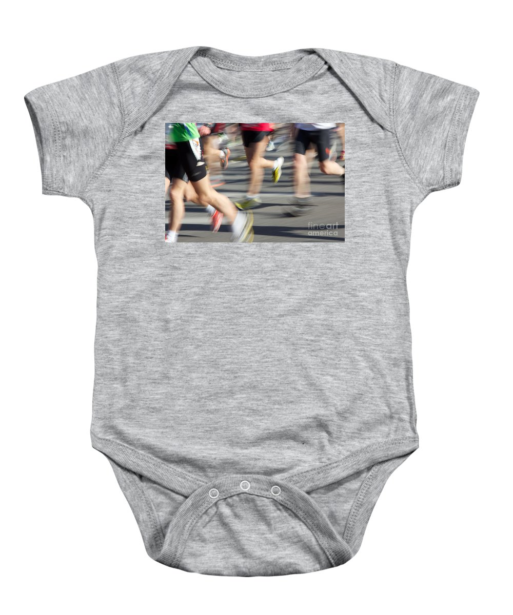 28th Baby Onesie featuring the photograph Blurred Marathon Runners by Jannis Werner