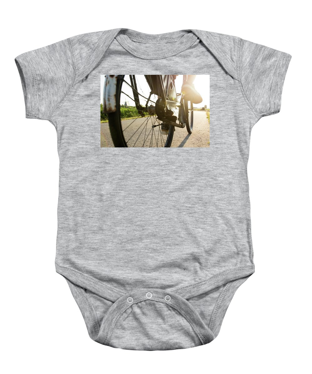 Wheel Baby Onesie featuring the photograph Close Up Of Wheel Of Bicycle On Road by Andres Valencia