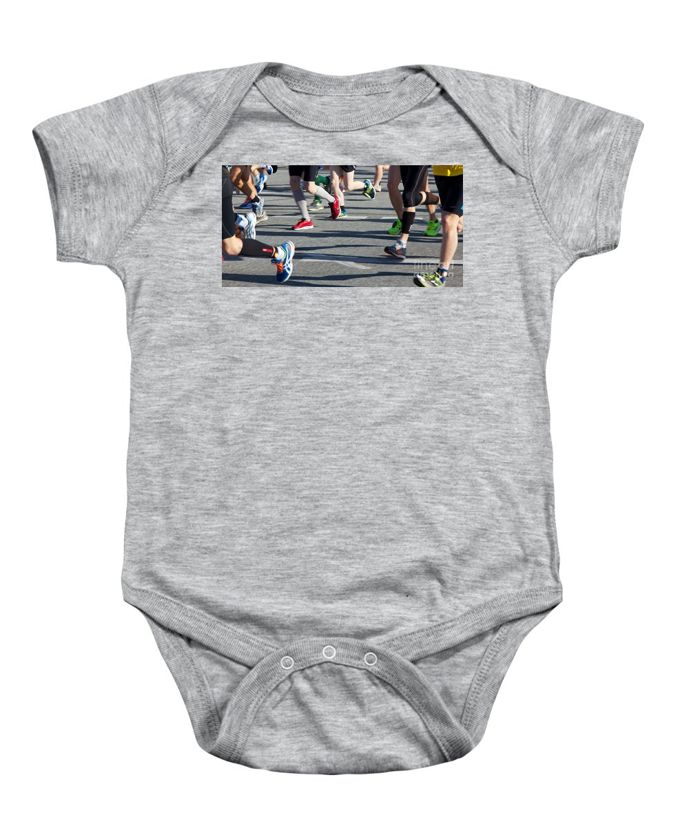 28th Baby Onesie featuring the photograph Legs Of Runners At Marathon by Jannis Werner