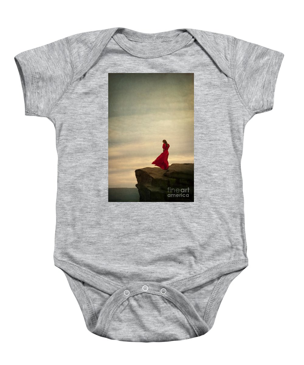 Woman Baby Onesie featuring the photograph Woman In A Vintage Red Dress On A Windy Clifftop by Lee Avison