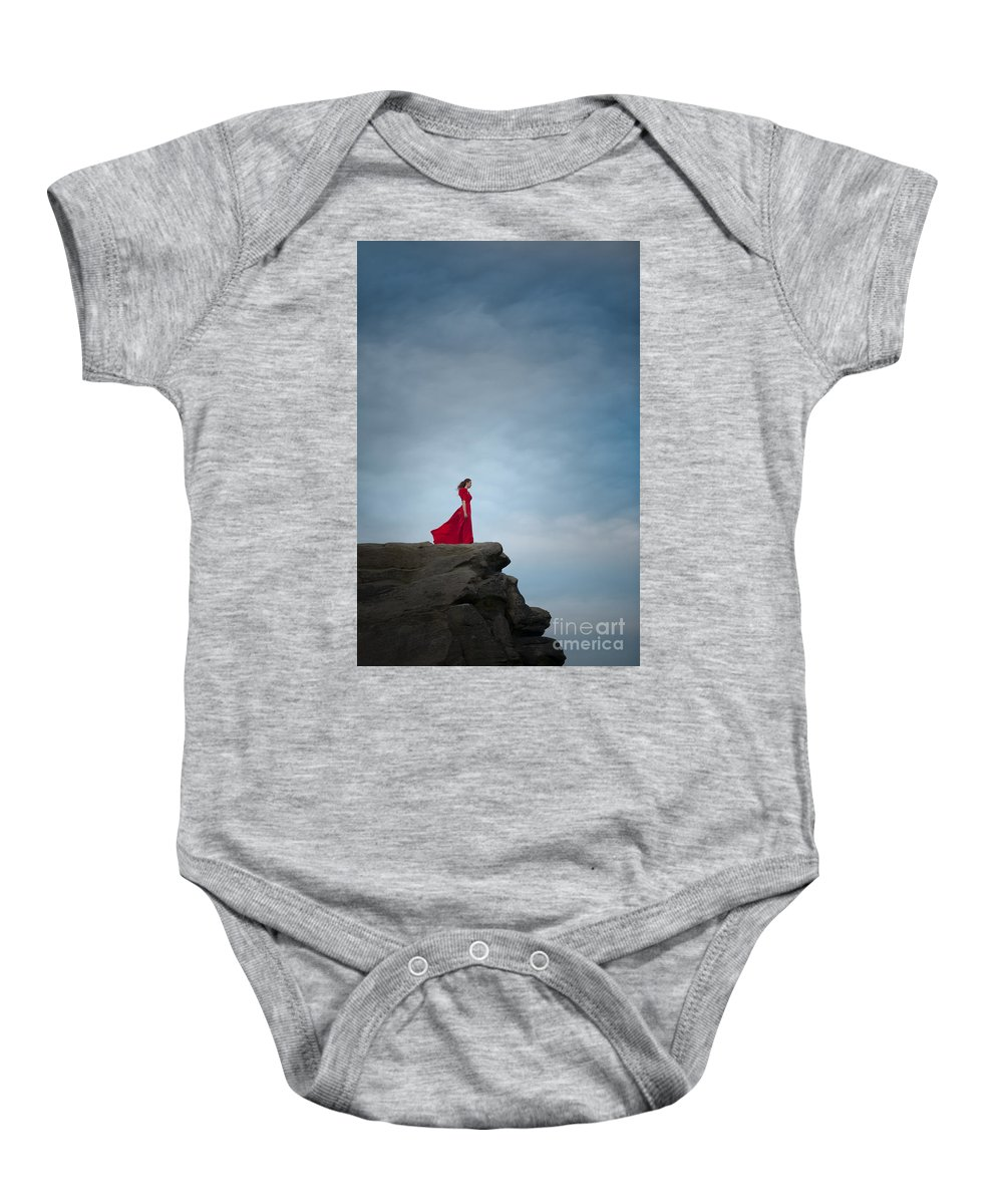 Woman Baby Onesie featuring the photograph Woman In Red Dress On A Clifftop by Lee Avison