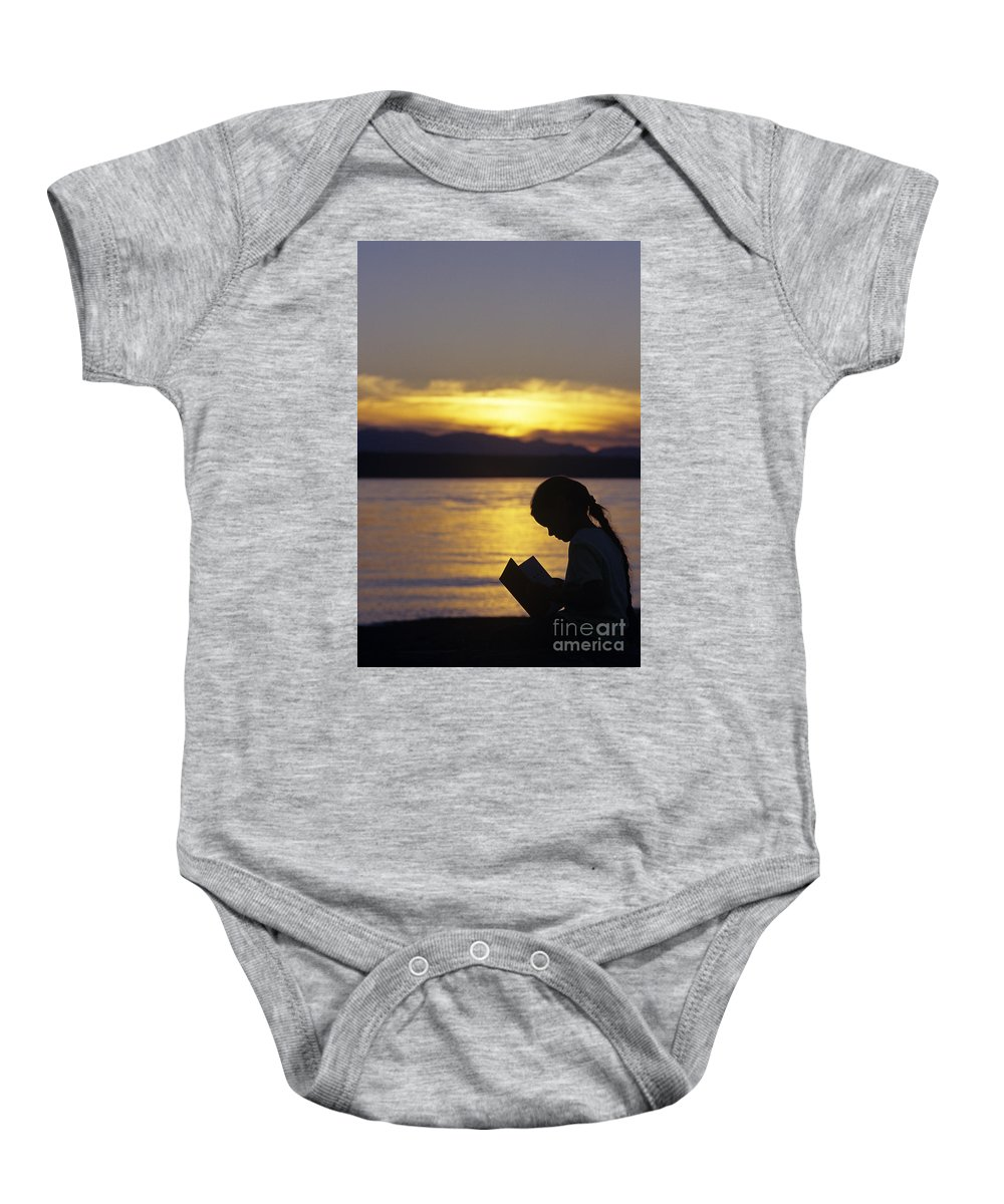Travel Baby Onesie featuring the photograph Young Girl Silhouetted Reading A Book On The Beach At Sunset by Jim Corwin