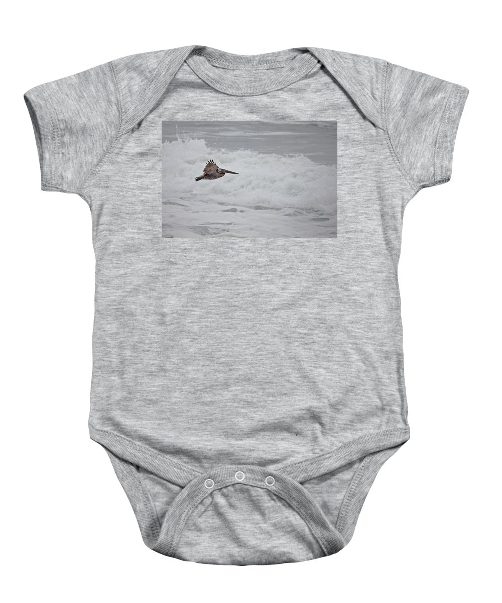 Pelican Baby Onesie featuring the photograph flying Pelican by Ralf Kaiser
