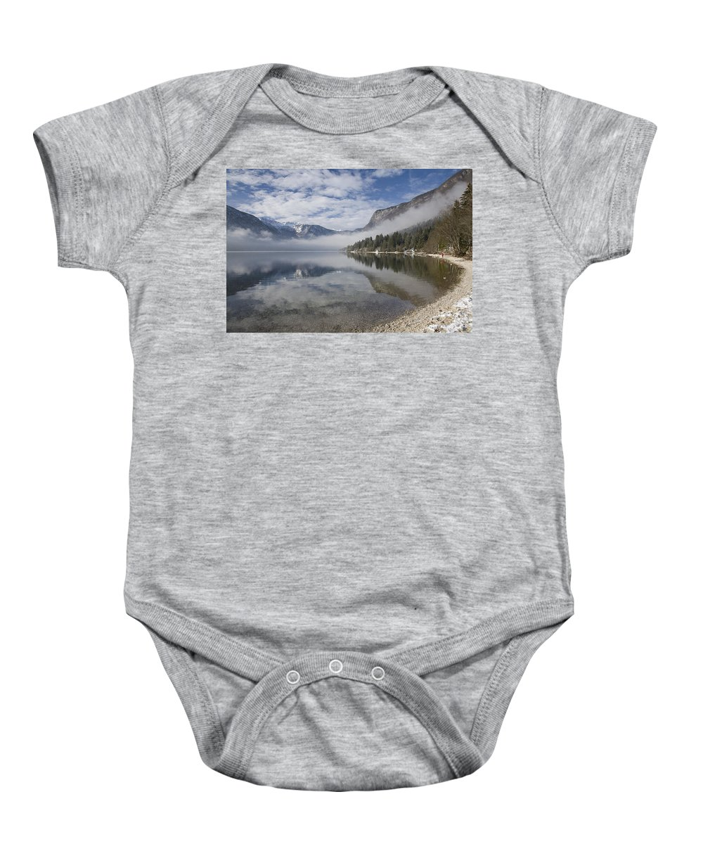 Bohinj Baby Onesie featuring the photograph mist burning off Lake Bohinj by Ian Middleton