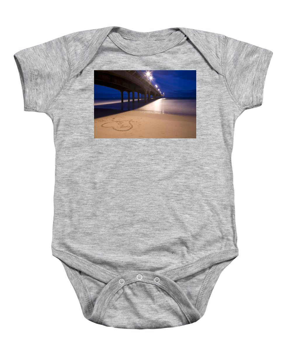 Boscombe Baby Onesie featuring the photograph Love Heart In The Sand At Boscombe Pier by Ian Middleton