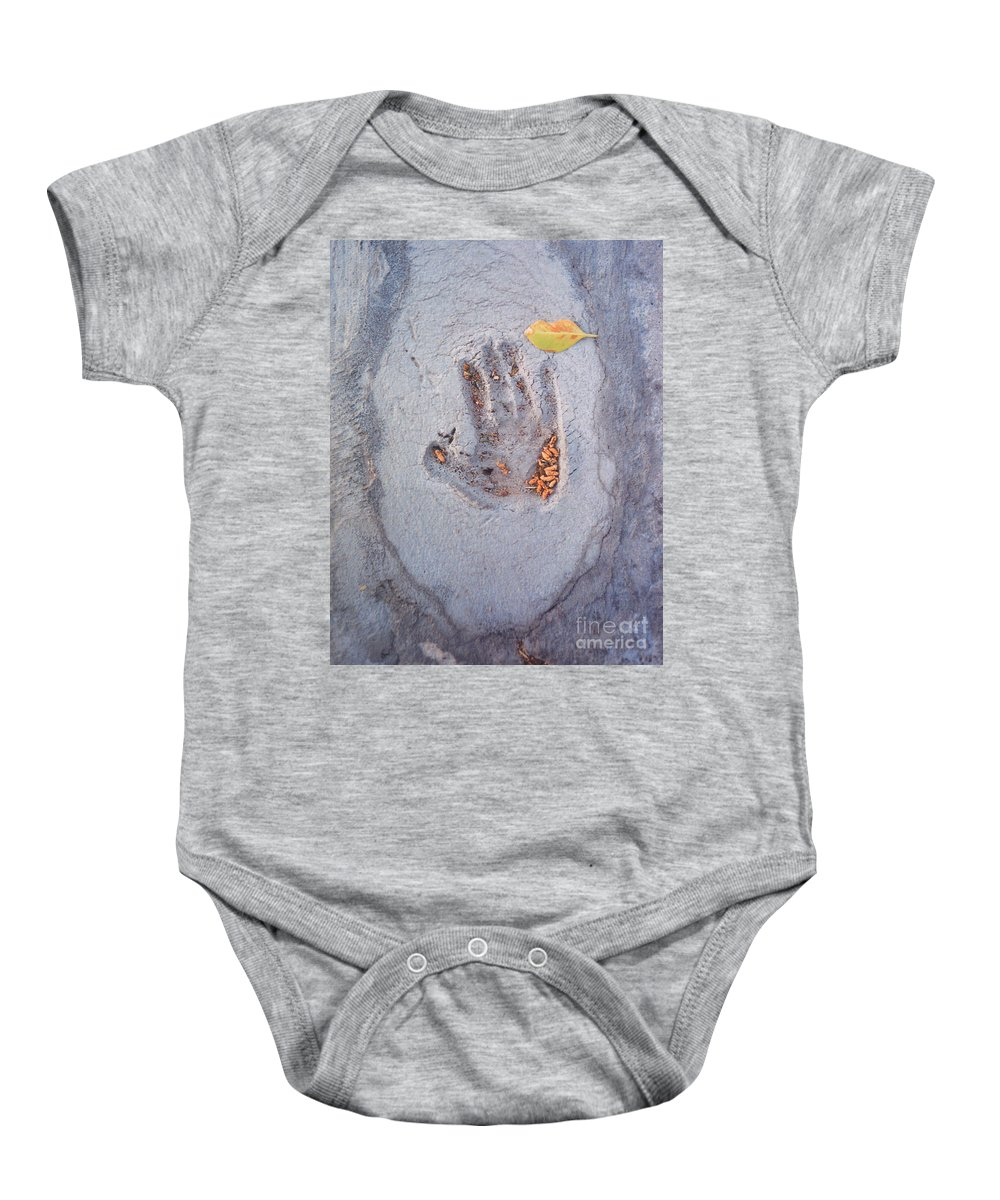 Baby Onesie featuring the photograph Autumns Child Or Hand In Concrete by Heather Kirk
