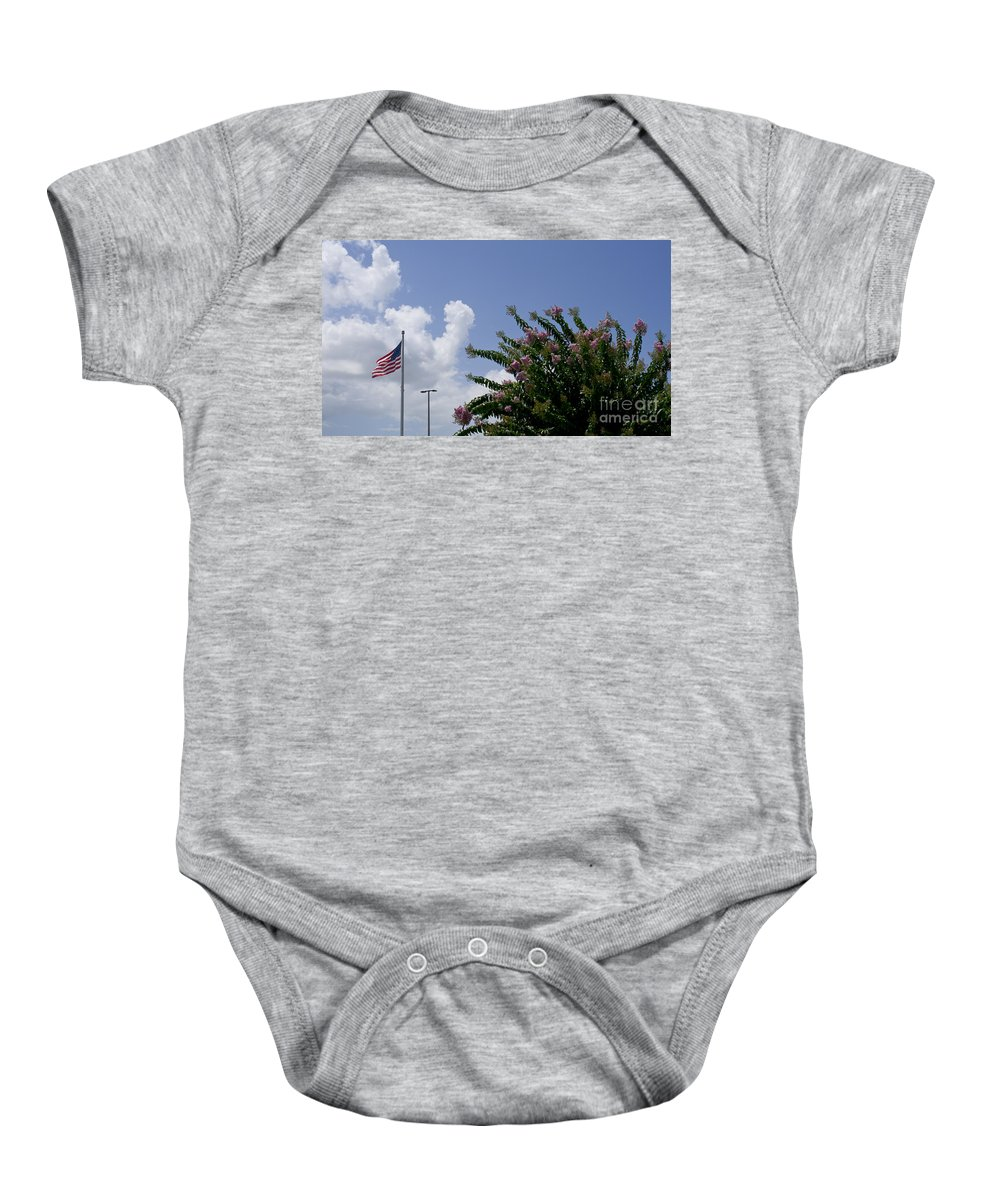 Flag Baby Onesie featuring the photograph Flag With Pink Flowers by Allan Hughes