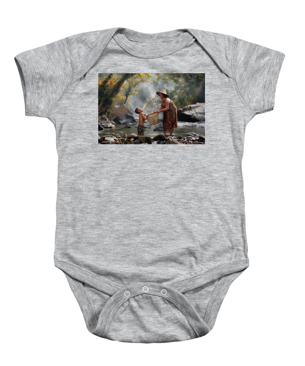 Family Baby Onesie featuring the photograph Mother And Son Are Happy With The Fish In The Natural Water by Somchai Sanvongchaiya