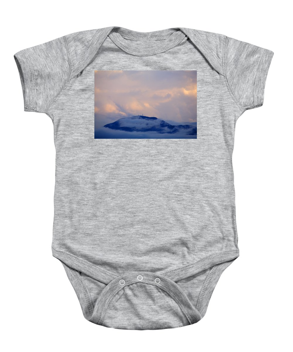 Storm Baby Onesie featuring the photograph Storm Clouds Gather Over Mountains by Ian Middleton
