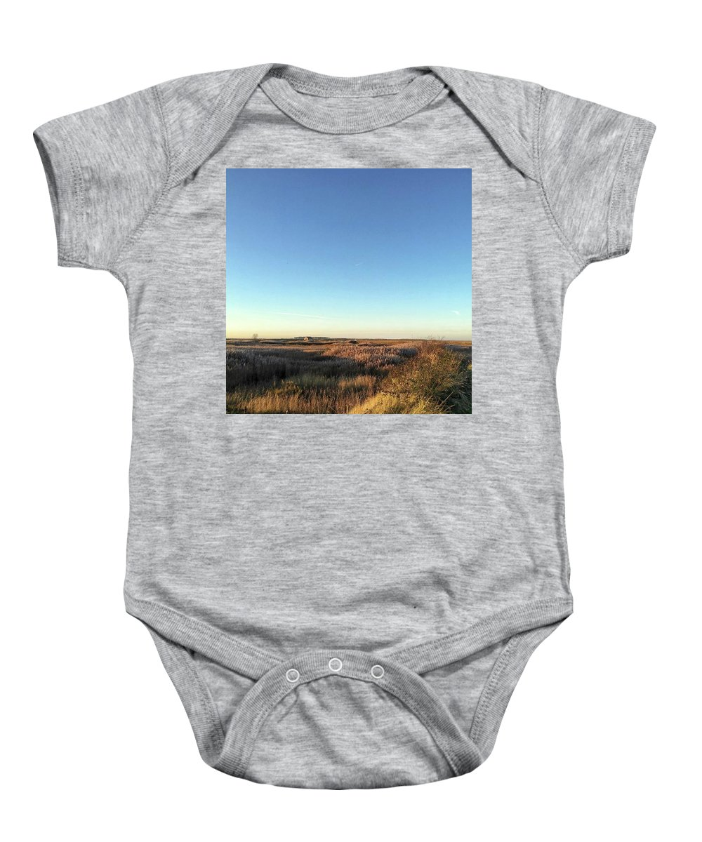 Natureonly Baby Onesie featuring the photograph Thornham Marsh Lit By The Setting Sun by John Edwards
