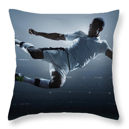 Goal Throw Pillow featuring the photograph Soccer Player Kicking Ball In Stadium by Dmytro Aksonov