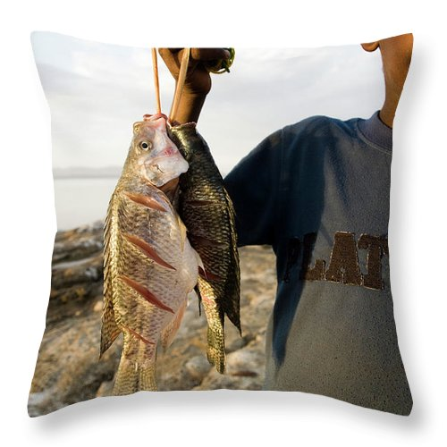 Africa Throw Pillow featuring the photograph A Boy Smiles While Holding A String by Michael Hanson