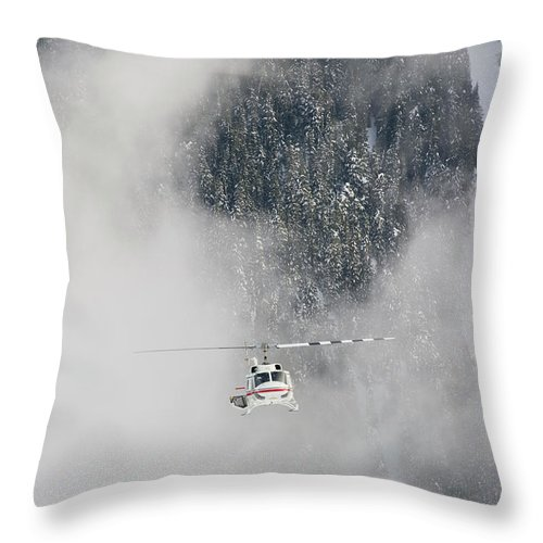 British Columbia Throw Pillow featuring the photograph A Heli-ski Helicopter Flies by Topher Donahue