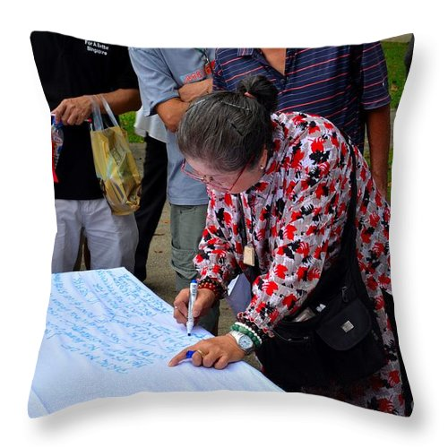 Lady Throw Pillow featuring the photograph A Lady Signs Petition At May Day Rally Singapore by Imran Ahmed