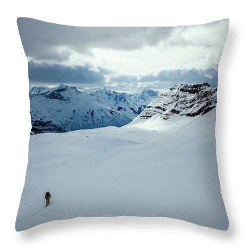 Cold Temperature Throw Pillow featuring the photograph A Man Ski Touring Near Icefall Lodge by Mike Schirf