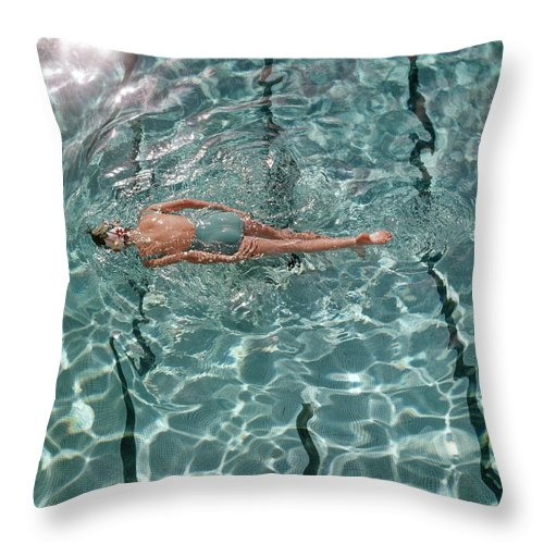 Water Throw Pillow featuring the photograph A Woman Swimming In A Pool by Fred Lyon