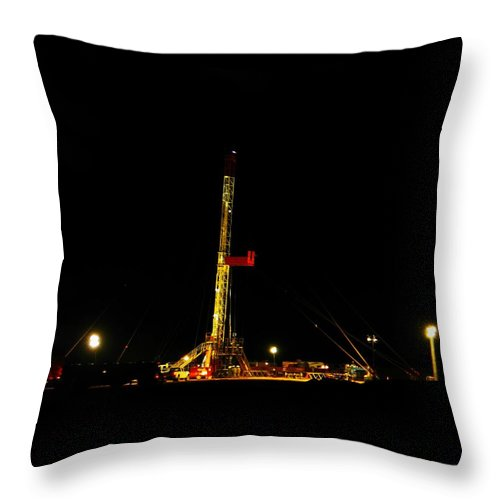Oil Rigs Throw Pillow featuring the photograph A Workover Rig At Night by Jeff Swan