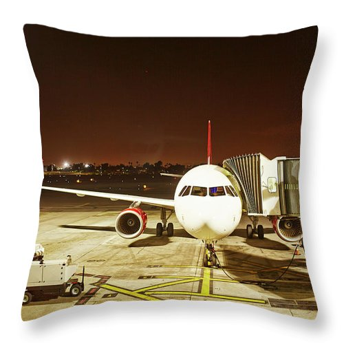 Passenger Boarding Bridge Throw Pillow featuring the photograph Airplane Parked At Jetway by Ballyscanlon