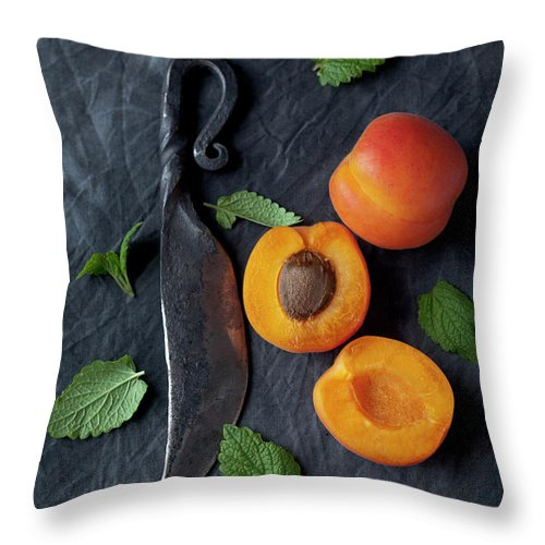 Orange Color Throw Pillow featuring the photograph Apricots With Leaves And Knife On Black by Westend61