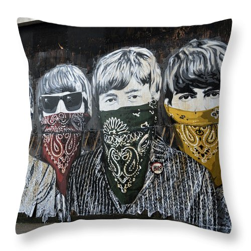Banksy Throw Pillow featuring the photograph The Beatles wearing face masks street mural by RicardMN Photography