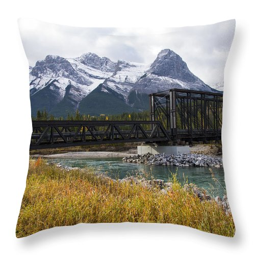 Canmore Canada Iron Bridge Railroad Bridges Trestle Trestles Mountain Rocky Mountains Cloud Clouds Grass Grasses Bow River Rivers Canadian Rockies Snow Peak Peaks Rock Rocks Stone Stones Throw Pillow featuring the photograph Bow River Railroad Trestle by Bob Phillips