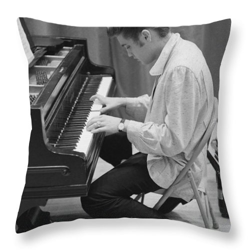 Elvis Presley Throw Pillow featuring the photograph Elvis Presley on piano while waiting for a show to start 1956 by The Harrington Collection