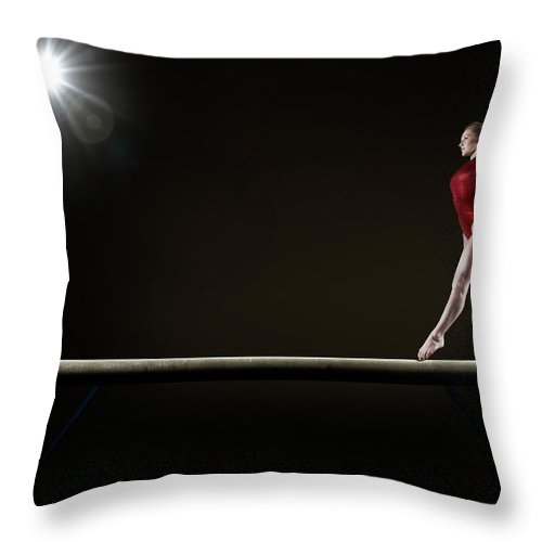 Human Arm Throw Pillow featuring the photograph Female Gymnast Balancing On Beam by Mike Harrington