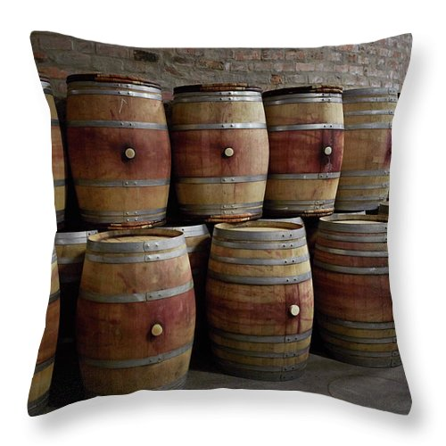 Stellenbosch Throw Pillow featuring the photograph French Wine Barrels Stacked At Winery by Klaus Vedfelt