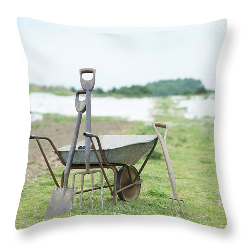 Grass Throw Pillow featuring the photograph Gardening Tools And Wheel Barrow On by Dougal Waters