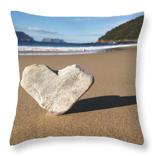 Water's Edge Throw Pillow featuring the photograph Heart Shaped Rock Sitting In Sand At by Jodie Griggs