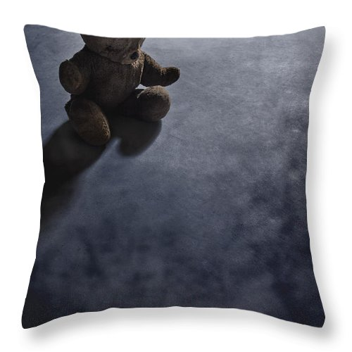 Teddy Bear; Bear; Toy; Sitting; Old; Vintage; Brown; Dirty; Plush; Floor; Cement; Alone; Desolate; Lost; Creepy; Mysterious; Depression; Youth; Shadow; Dark; Childhood Throw Pillow featuring the photograph Lost In The Darkness by Margie Hurwich