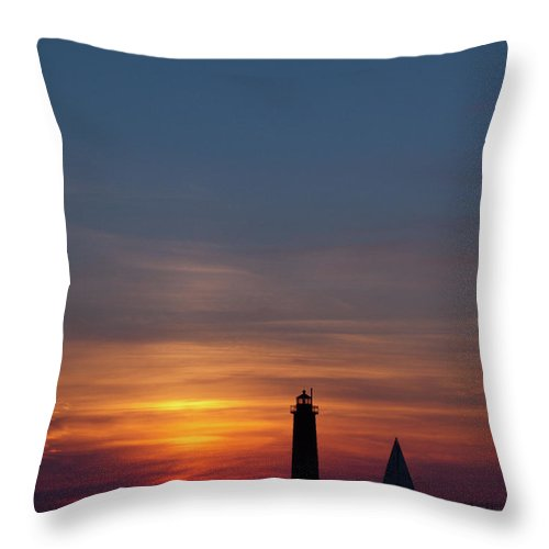 Sailboat Throw Pillow featuring the photograph Muskegon Lighthouse Silhouetted At Sunset With A Sailboat In The by John Harmon