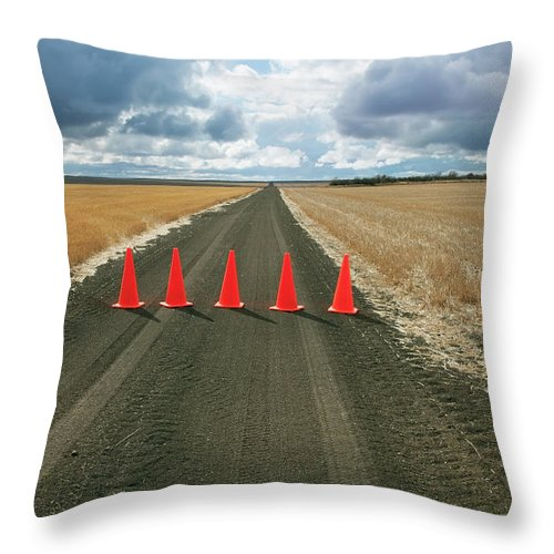 Orange Color Throw Pillow featuring the photograph Safety Cones Lined Up Across A Rural by Benjamin Rondel / Design Pics