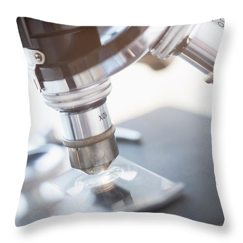 Microscope Throw Pillow featuring the photograph Studio Shot Of Microscope, Close-up by Tetra Images
