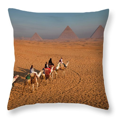 Working Animal Throw Pillow featuring the photograph Tourists On Camels & Pyramids Of Giza by Richard I'anson