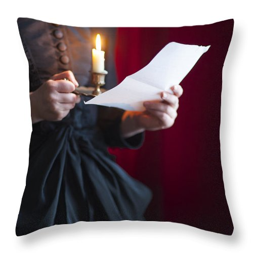 Woman; Victorian; Edwardian; 19th Century; 18th Century; Detail; Close Up; Mid Section; Indoors; Inside; Dress; Buttons; Hands; Hold; Holds; Holding; Alone; Single; One; Read; Reads; Reading; Letter; Paper; Correspondence; Message; Love Letter; Candle; Candlelight; Light; Lit; Candle Holder; Wee Willie Winkie; Black; Red Throw Pillow featuring the photograph Victorian Woman Reading A Letter By Candle Light by Lee Avison