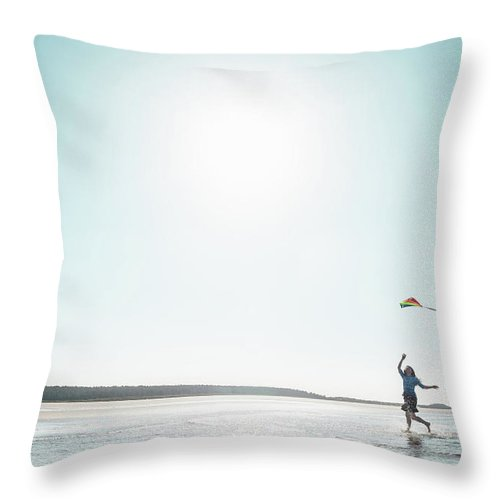 Three Quarter Length Throw Pillow featuring the photograph Woman Flying Kite On Beach by Dan Brownsword