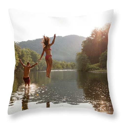 Young Men Throw Pillow featuring the photograph Young Couple Jumping Into River by Zave Smith