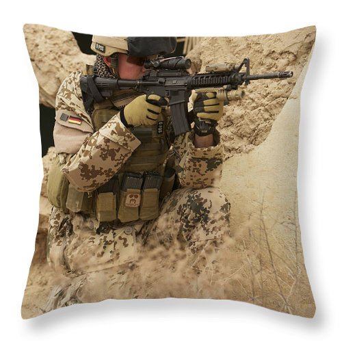 Looking Through Throw Pillow featuring the photograph A German Army Soldier Armed With A M4 by Terry Moore