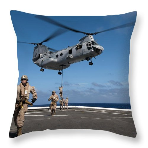 Warship Throw Pillow featuring the photograph Marines Fast Rope On To The Flight Deck by Stocktrek Images