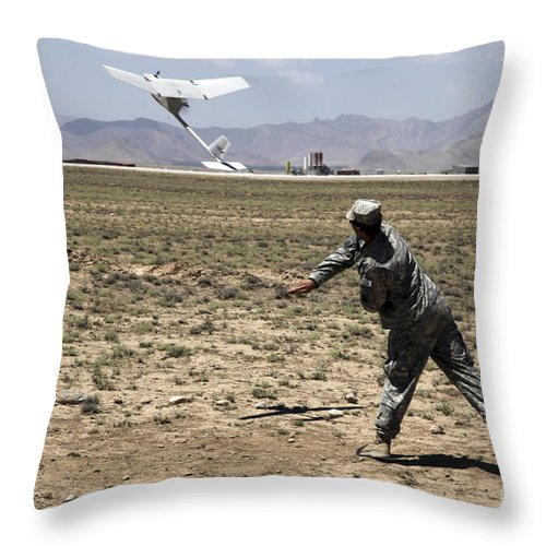 Military Throw Pillow featuring the photograph U.s. Army Soldier Launches An Rq-11 by Stocktrek Images