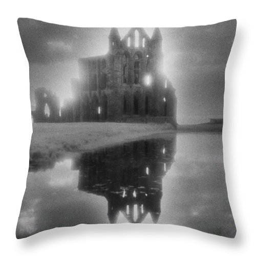 Eerie; Atmospheric; Spooky; Haunted; Haunting; Dramatic; Striking; Misty; Hazy; Lake; Reflection; English; Architecture; Exterior; Ruin; Ruins Throw Pillow featuring the photograph Whitby Abbey by Simon Marsden