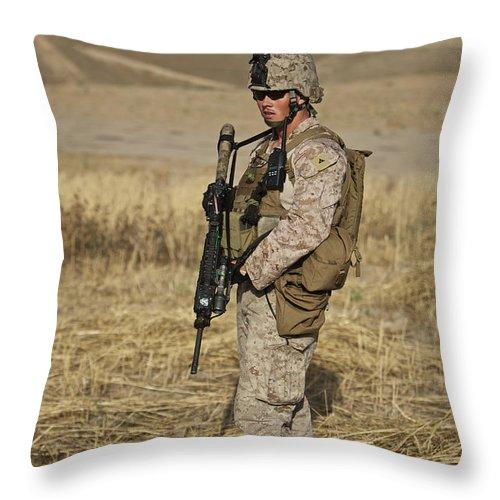 Field Throw Pillow featuring the photograph U.s. Marine Patrols A Wadi Near Kunduz by Terry Moore