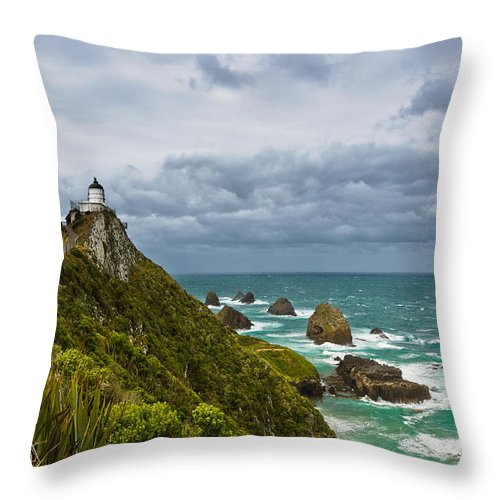 Beach Throw Pillow featuring the photograph Nugget Point Light House And Dark Clouds In The Sky by U Schade