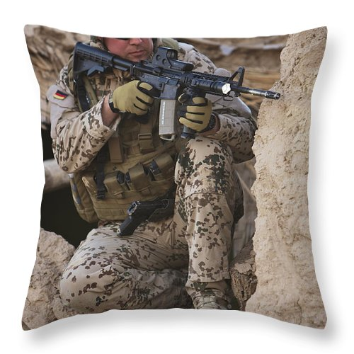 Sitting Throw Pillow featuring the photograph A German Army Soldier Armed With A M4 by Terry Moore