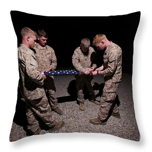 Folding Throw Pillow featuring the photograph U.s. Marines Fold The American Flag by Terry Moore