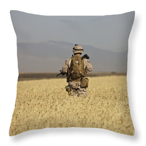 Wheat Throw Pillow featuring the photograph U.s. Marine Patrols A Wadi Near Kunduz by Terry Moore